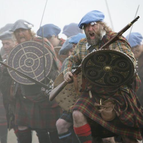 Rekonstrukce skotských horalů s mušketou a dalšími zbraněmi v moderním reenactmentu.