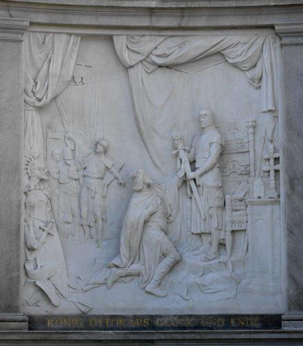 """""""Pokleknutí Přemysla Otakara před Rudolfem"""" na reliéfu pomníku ve vídeňských zahradách (Volksgarten) s nápisem (v překladu): Štěstí a konec krále Otakara."""