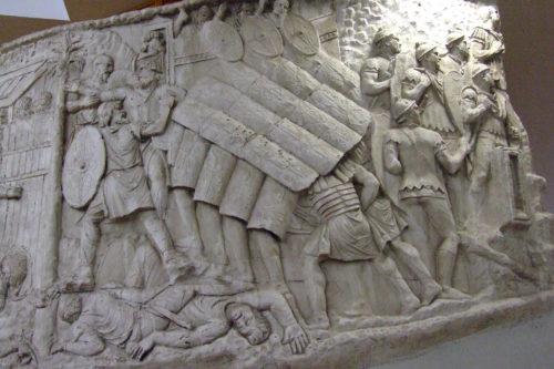 Obranná formace proti šípům či oštěpům zvaná želva čili testudo na Traiánově sloupu v Římě