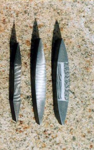 Průřezy čepelí ze svářkového damasku, dvě vlevo jsou z čistě z damasku, na průřezu vpravo je vidět měkké jádro, které se používalo nejčastěji