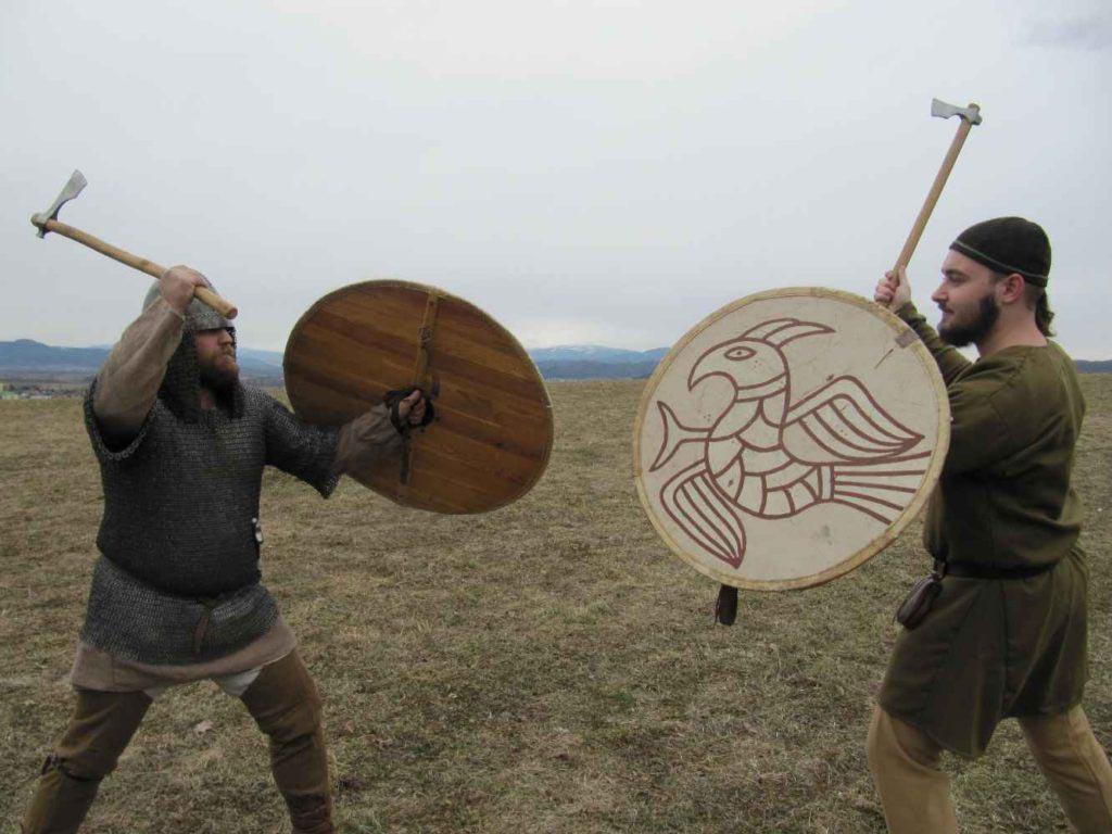 Dva bojovníci s jednoruční sekerou a štítem na začátku souboje.