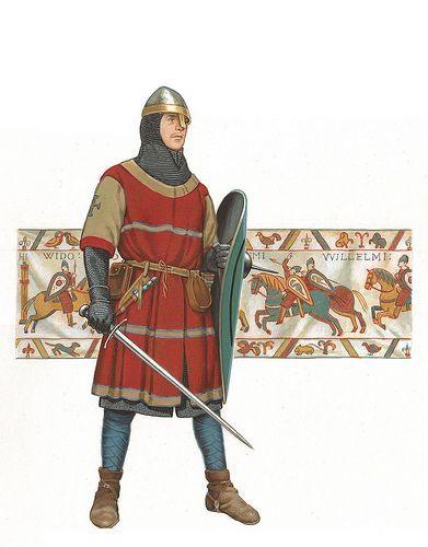 Rekonstrukce normanského rytíře z 11. století s velkým štítem a dlouhým mečem v kroužkové zbroji a typické normanské přilbě. Podobní bojovali jak proti Byzanci, tak v bitvě u Hastings roku 1066