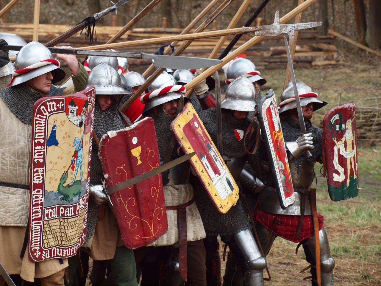 Čelo pěšího husitského šiku tvořili bojovníci s meči a pavézami, za nimi je doplňovali ti s dlouhými ratišťovými zbraněmi – především sudlicemi