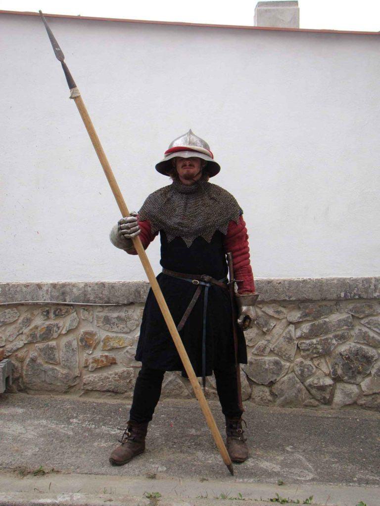 """Obyčejný husitský pěšák v klobouku, prošívaném kabátci a kroužkovém """"oboječku"""" (límci) s kopím"""