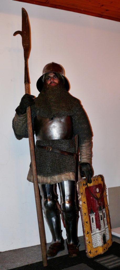 Lépe vybavený pěšák z doby husitských válek v plátové zbroji kombinované s kroužkovou. Na hlavě má hluboký klobouk, v jedné ruce sudlici a ve druhé pavézu