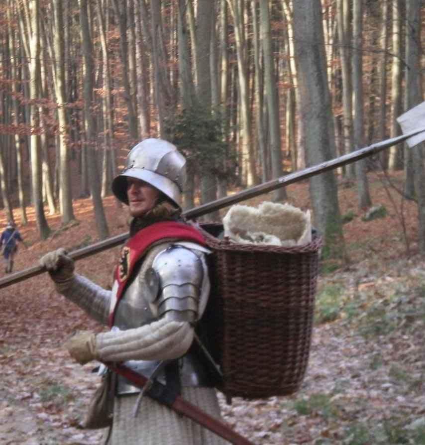 """Jan """"Bídy"""" Biederman v plátové zbroji s halapartnou v ruce a nůší na zádech na pochodu"""